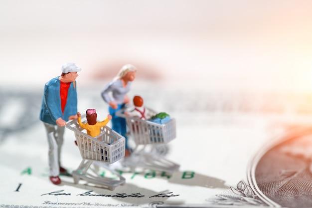 支払およびオンラインでの購入としてドル紙幣の上を歩く買い物客