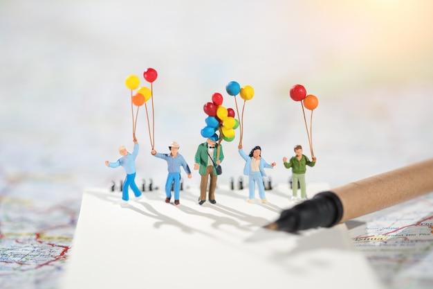 Группа счастливой семьи держит воздушный шар с помощью карты и путешествия на праздник идея концепции семейного дня