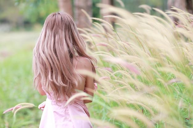 幸せな時間を過ごして、自然の中の芝生のフィールドの間で楽しんでいる美しい女性の肖像画