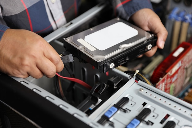 技術者の男修正またはコンピューターのハードディスクのアップグレード
