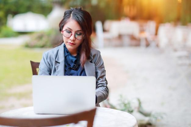 Милая и очаровательная деловая женщина в очках работает на ноутбуке из ресторана или кафе