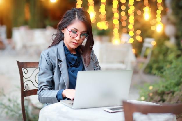 レストランやカフェからラップトップコンピューターに取り組んでいるメガネのかわいい、魅力的な女性実業家