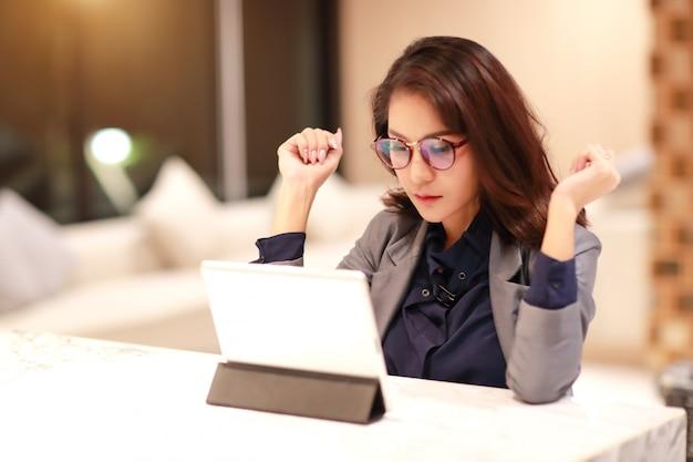 タブレットを使用してメガネと働くと魅力的な女性(自宅のコンセプトから仕事)