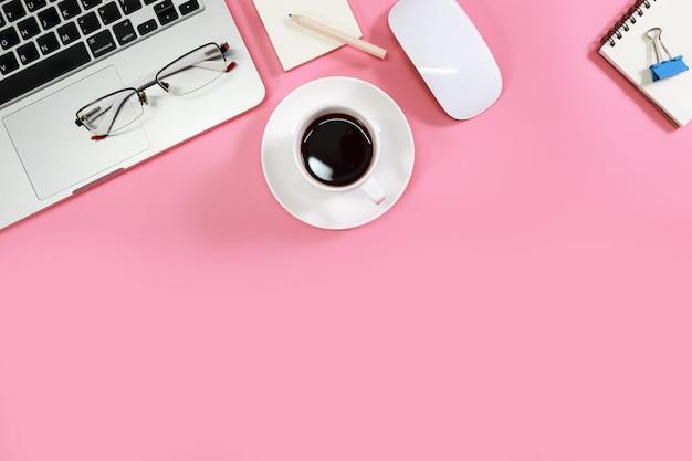 ピンクのラップトップコンピューターとフラットレイアウトワークスペーステーブル