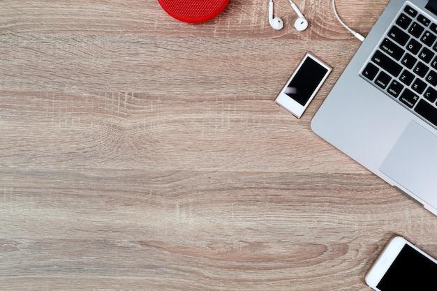 ラップトップコンピューターとイヤホン付き作業木製テーブル