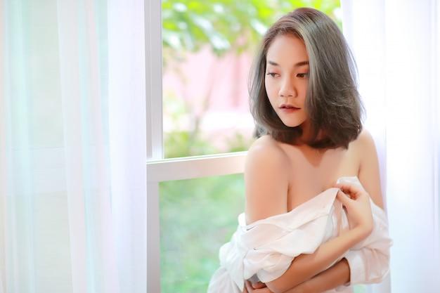 朝のウィンドウで美しく、セクシーな女性の肖像画