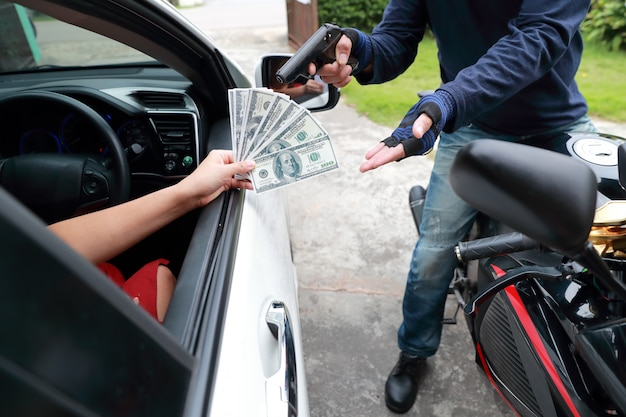 車の中で女性からお金を盗むバイクに銃を持つ泥棒