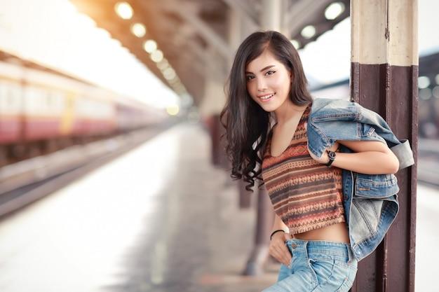 Молодой путешественник женщина с курткой жан ждет поезд