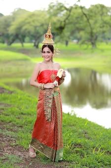 手にステアリングホイールの花を持つ古代寺院のタイの伝統的な衣装でアジアの女の子をファッションします。