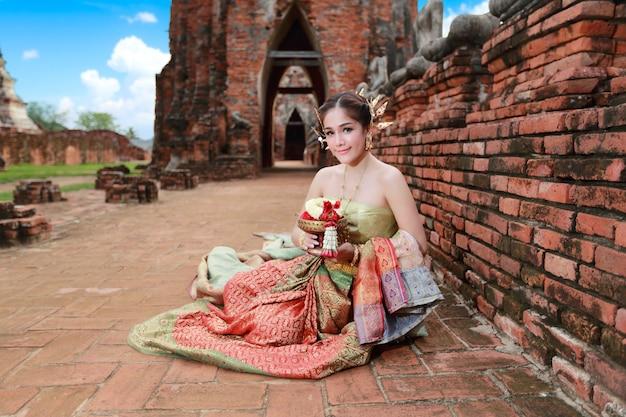 Фасонируйте азиатскую девушку в тайском традиционном костюме в древнем храме с цветком рулевого колеса в руке