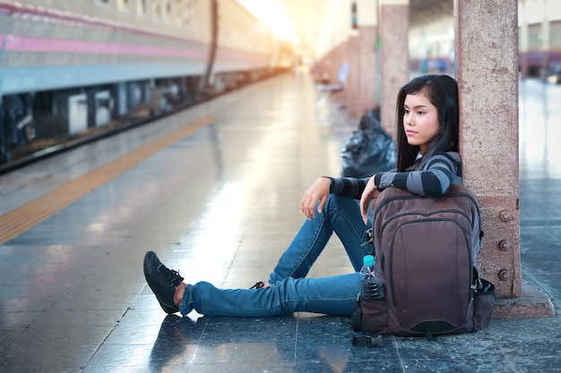 Молодой путешественник женщина сидит и ждет поезд