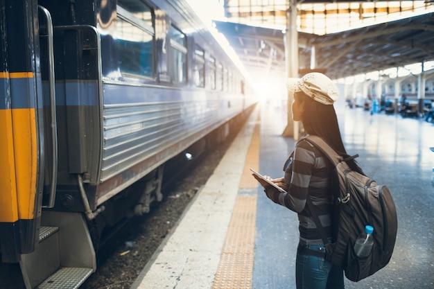 電車を待っているバックパックを持つ若い旅行者女性