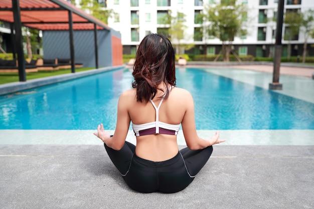 若い健康でスポーティな女性は屋外ヨガストレッチを行う