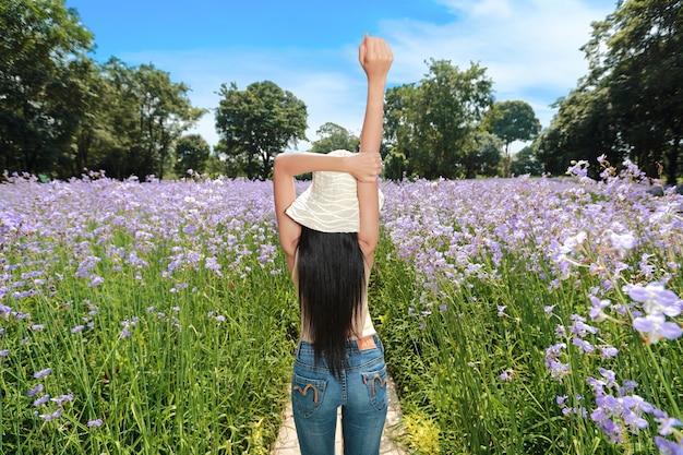 美しい少女は、澄んだ青い空に満足しながら、自然に植えられたナガクサ花の真ん中に腕を持ち上げます