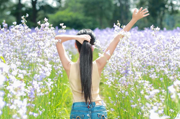 幸せな時間を過ごして、自然の中で花ナガ紋付きフィールドの間で楽しんでいる美しい女性の背面図の肖像画