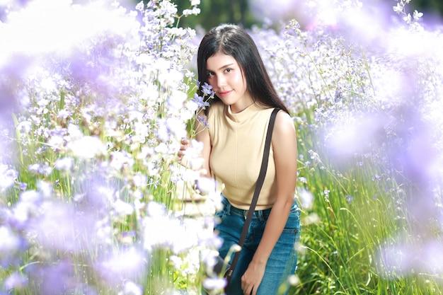 Портрет красивой женщины, имеющие счастливое время и наслаждаясь среди цветов нага-хохлатая поля в природе