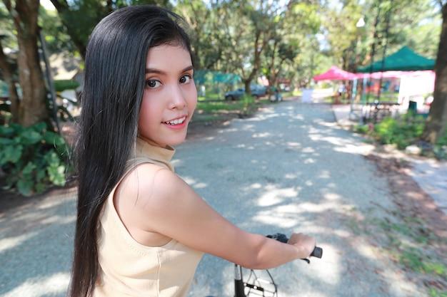 自転車に乗って、自然の中で楽しんで美しいと流行に敏感な若い女性の肖像画