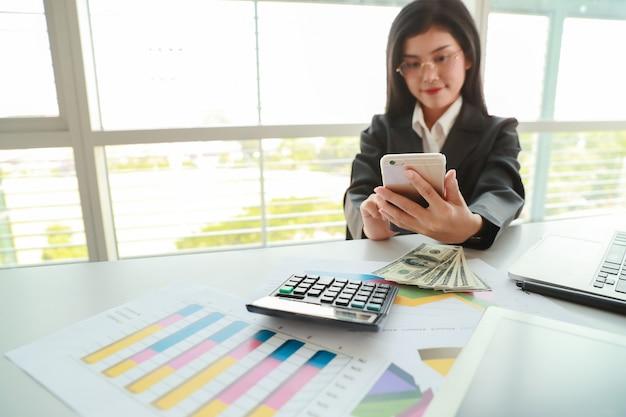 Коммерсантка используя сотовый телефон и компьютер пока работающ на сводном отчете компании с диаграммой