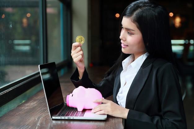 ピンクの貯金箱にビットコインまたはコインを示す実業家の肖像画。