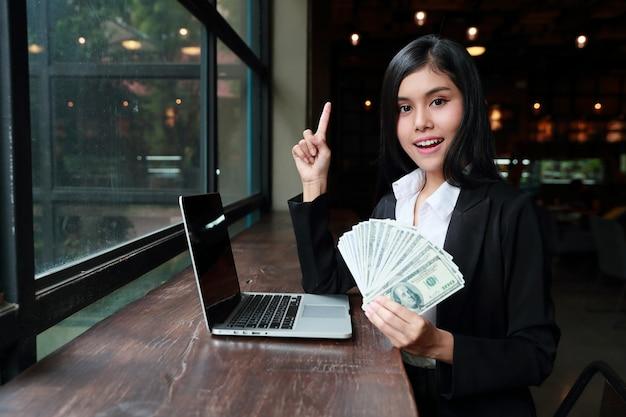 テーブルの上のコンピューターで手にお金を示す実業家。