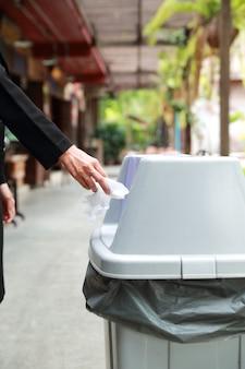 Крупным планом женщина рука бросает кусок бумаги в мусор