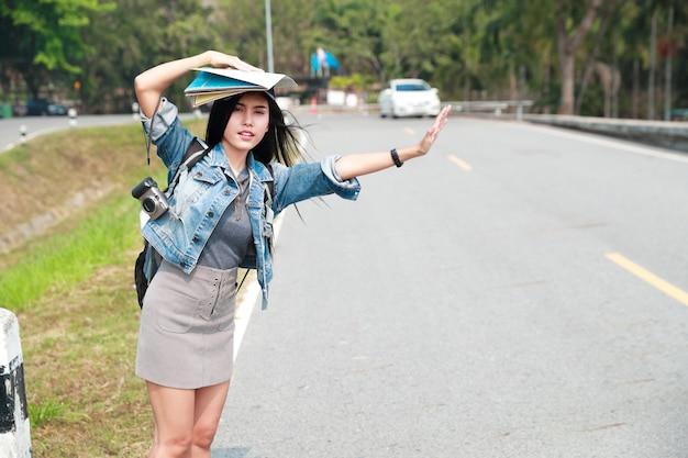 休暇中に旅行中に道路上の車を待っているバックパックを持つ若いアジア旅行者