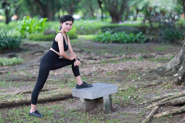 健康的でスポーティな若い女性は屋外ヨガストレッチ