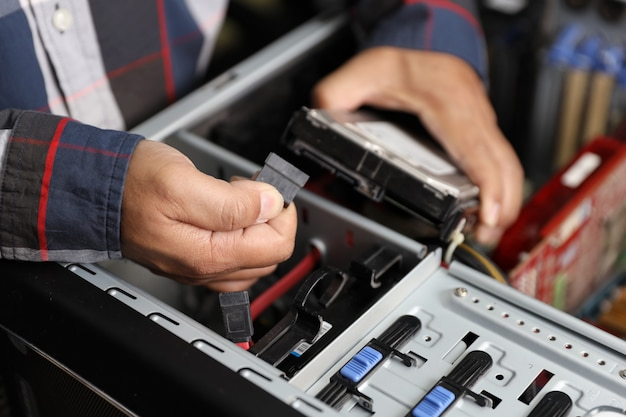 技術者の男は、コンピュータのケーブルを抜くか差し込むことで、ハードディスクを修正またはアップグレードします。