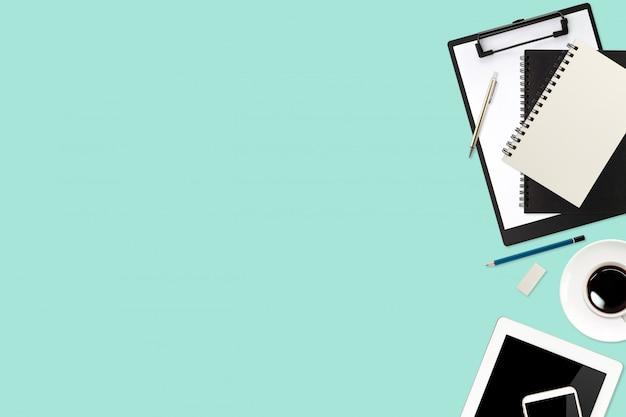 ラップトップコンピューター、オフィス用品タブレット、携帯電話、コーヒーカップを使用してフラットレイアウトまたはトップビューワークスペースビジネスグリーンデスク