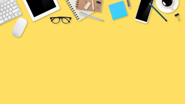 ラップトップコンピューター、事務用品、コーヒーカップ、タブレット、黄色のパステルの携帯電話でフラットレイアウトワークスペーステーブル