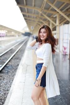 完全な長さの若いアジアの女性に立って、駅で待っている間カメラを見て