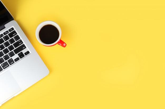 ワークスペースのラップトップコンピューターと赤いコーヒーカップを持つ単純なビジネスオフィステーブルのトップビュー