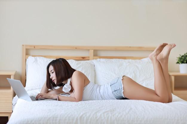 ベッドに横になっている白いドレスで美しい大人のアジア女性の側面図ショット。