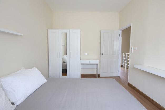柔らかく透明な光のある寝室の新しいモダンな白いベッド