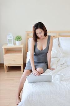コンピューターに取り組んでいる灰色のセクシーなドレスで完全な長さの成人自営業のアジア女性
