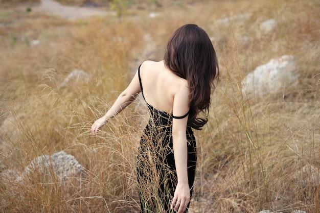 若いアジア女性、平和と乾いた草の中で山を歩いて黒いドレスの長い髪の背面図