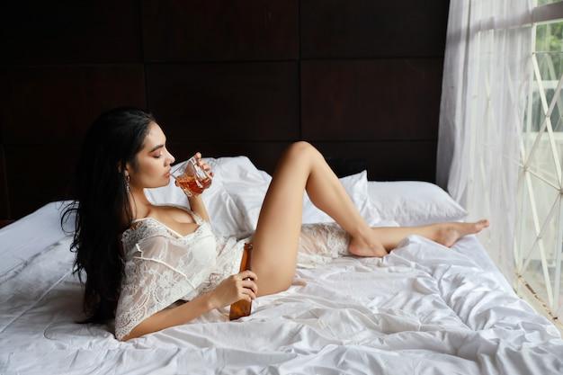 酒に酔ったアジアの女性がベッドに横たわっている間アルコールを飲む