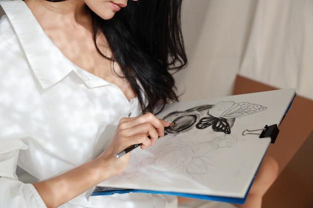 アジアのアーティストの女性の手が鉛筆で絵を描く
