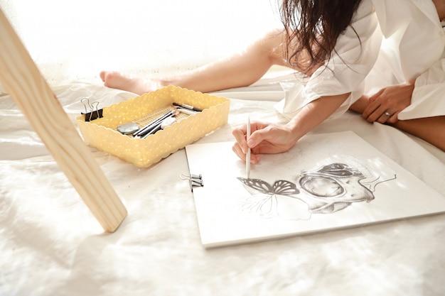 アジアのアーティストの女性が座っている間鉛筆で絵を描く