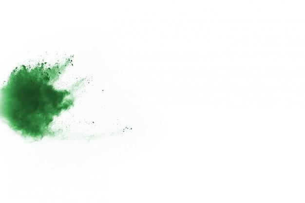 Взрыв зеленого порошка на белой предпосылке.