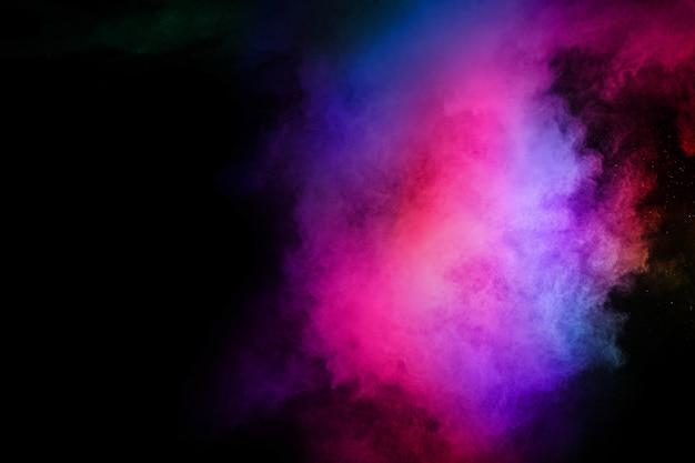 Абстрактный цветной взрыв пыли на черном.
