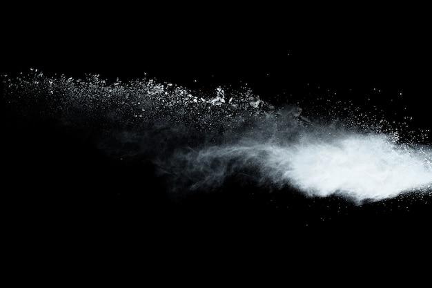 Взрыв белого порошка на черном фоне