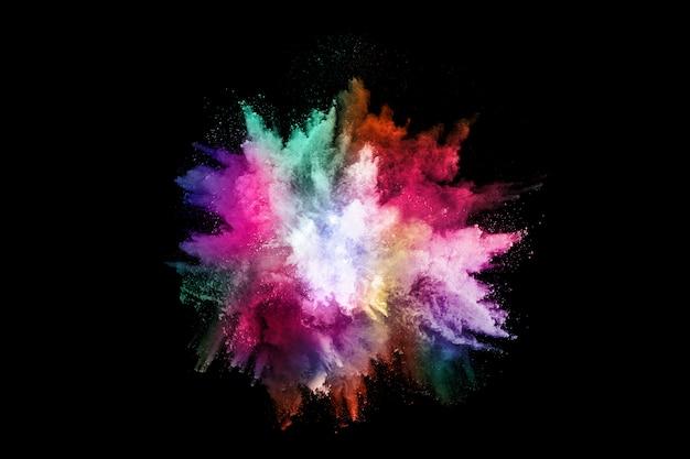 Абстрактный цветной взрыв пыли на черном фоне.