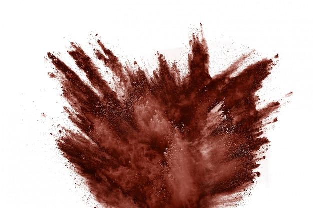 Взрыв порошка коричневого цвета на белом фоне.