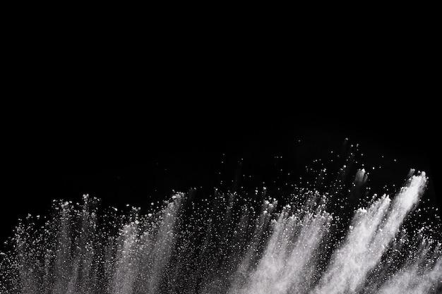 黒い背景に白い粉の爆発。色付きの雲。カラフルな粉塵が爆発します。ペイントホーリー。