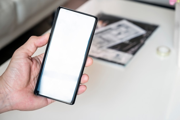 空白の画面を持つスマートフォンを持っているクローズアップ男の手、テキストまたは製品の表示用のスペースをコピーします。