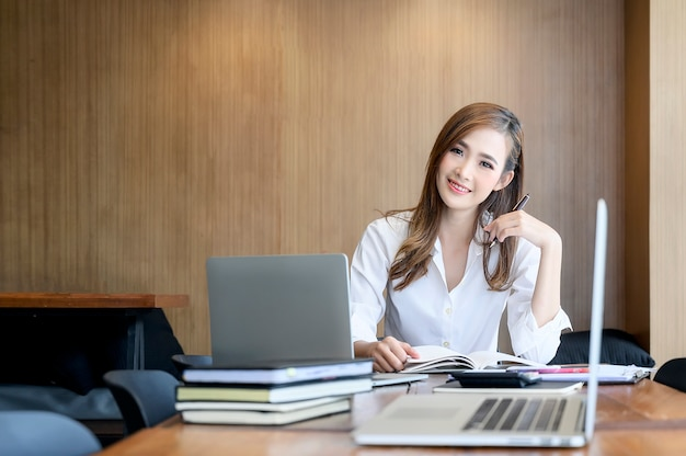 Портрет молодой женщины в белой рубашке, улыбаясь и глядя в камеру, сидя на рабочий стол