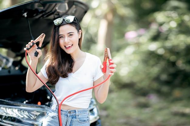笑みを浮かべて、バッテリージャンパーケーブルを示す美しい女性