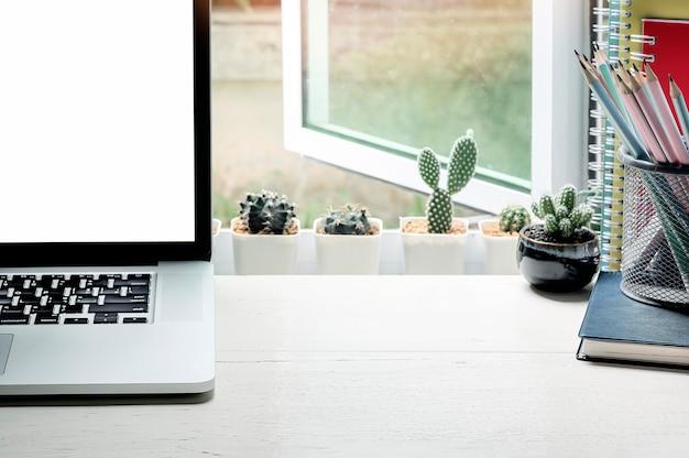 Макет ноутбук с пустой экран, карандаш и кактус на деревянный стол возле окна с солнечным светом.