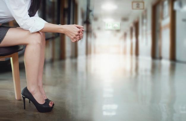 病院で座って、医者を待っている間彼女の手を強調した女性を強調しました。